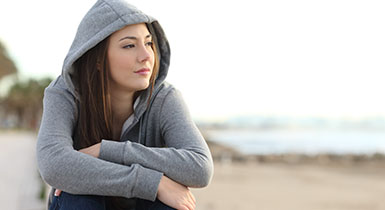 Teenage girl in hoodie sweatshirt looking away